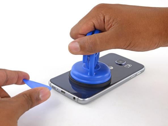 ساکشن کاپ را به سمت بالا بکشید و شدت نیروی کششی را به تدریج تا جایی افزایش دهید که شکاف باریکی در لبه زیرین قاب گلکسی S6 Edge ایجاد شود. اگر احساس کردید بدنه گوشی با کشیدن ساکشن کاپ بلند میشود، سعی کنید با نوک اسپاتول لبه زیرین بدنه گوشی را نگه دارید و همزمان با این کار ساکشن کاپ را به سمت بالا بکشید.