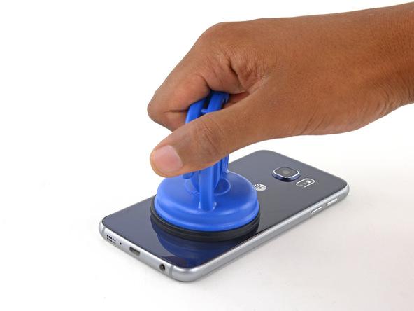 گلکسی اس 6 تعمیری را روی میز کارتان قرار داده و ساکشن کاپ را به سمت بالا بکشید. شدت نیروی کششی را به تدریج تا جایی افزایش دهید تا شکاف باریکی روی لبه زیرین قاب گوشی ایجاد شود.