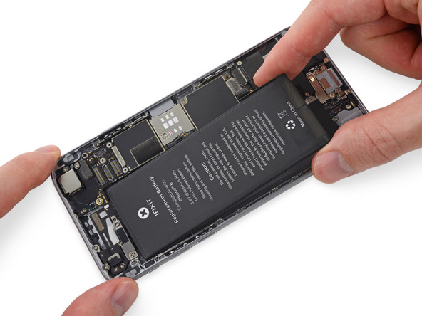 به آرامی لبه فوقانی باتری آیفون را در لبه جایگاهش بر روی قاب پشت گوشی قرار دهید تا کانکتورهای باتری و برد به هم متصل شوند. سپس لبه زیرین باتری را هم روی قاب پشت گوشی قرار دهید تا باتری آیفون کاملا بر روی جایگاه خودش بنشیند.