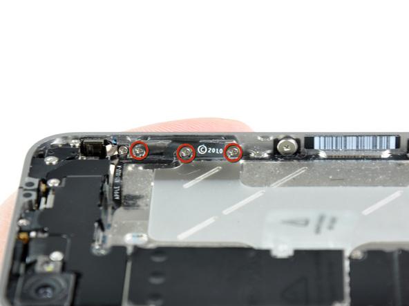 سه پیچی که در عکس با رنگ قرمز مشخص شدهاند را باز کنید. این پیچ ها براکت دکمه ولوم آیفون 4 تعمیری را روی لبه قاب گوشی محکم میکنند.