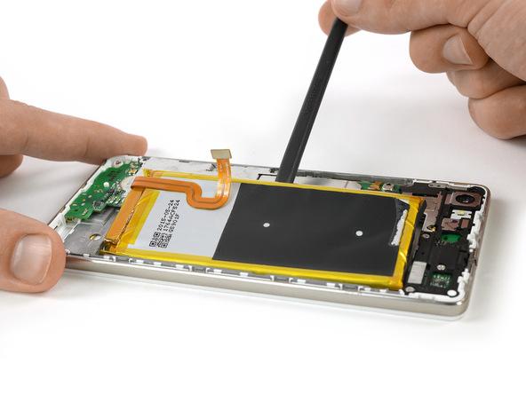 به آرامی نیروی بیشتری را با اسپاتول یا قاب باز کن پلاستیکی به باتری وارد کنید تا لبه سمت چپ آن کاملا از روی جایگاهش بلند شود.