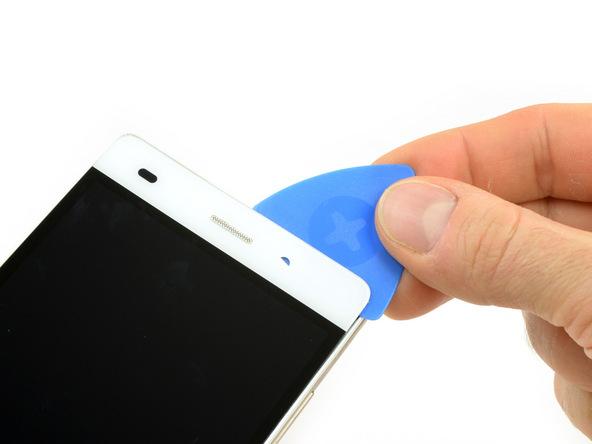 نوک پیک را به آرامی از لبه فوقانی قاب هوآوی P8 Lite تعمیری به داخل شکاف مابین ال سی دی و بدنه اصلی آن فرو ببرید. پیک را در این قسمت حرکت دهید تا لبه فوقانی ال سی دی گوشی شل شود.