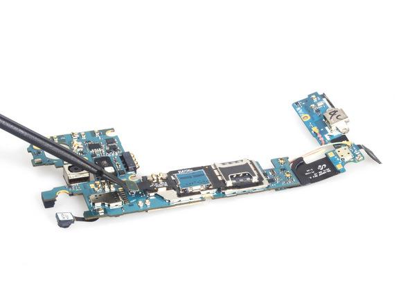 نوک اسپاتول سر پهن را خیلی آرام به زیر مجموعه خشاب سیم کارت و حافظه SD گوشی فرو ببرید و آن را با احتیاط به سمت جلو هول دهید تا مجموعه مور نظر کاملا از روی برد گوشی آزاد شود.