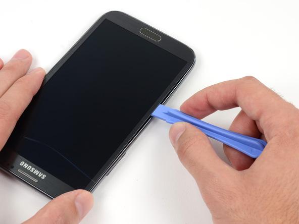 نوک قاب باز کن پلاستیکی را کاملا در لبه سمت چپ قاب گلکسی نوت 2 تعمیری حرکت دهید تا این بخش از قاب گوشی کاملا شل شود.