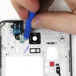 نوک قاب باز کن پلاستیکی یا یک پیک را به آرامی در زیر کانکتورهای جک هدفون فرو برده و سعی کنید کانکتورهای مذکور را از روی فریم میانی گوشی آزاد نمایید.