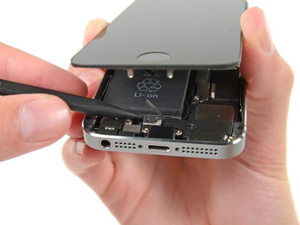آیفون SE تعمیری را به گونهای در دست بگیرید که قاب گوشی در لبه زیرین به مقدار کمی باز شده باشد. با دست مخالف خود نوک پنس یا اسپاتول را در سمت چپ براکت کانکتور دکمه هوم آیفون SE قرار دهید و به آرامی آن را به سمت بالا بکشید تا از جایگاهش خارج شود.
