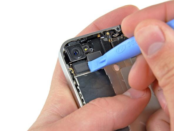 نوک قاب باز کن پلاستیکی را از گوشه سمت راست به زیر کانکتور لنز دوربین اصلی آیفون 4 تعمیری فرو ببرید و خیلی آرام این کانکتور را به سمت بالا هول دهید تا از روی سوکتش آزاد شود.