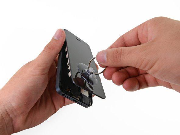 درب جلوی آیفون 5 تعمیری را به صورت کتابی از لبه زیرین باز کنید. زمانی که درب جلوی آیفون نسبت به درب پشت آن حالت عمودی پیدا کرد، آن را با کش به یک تکیهگاه مناسب وصل کنید.