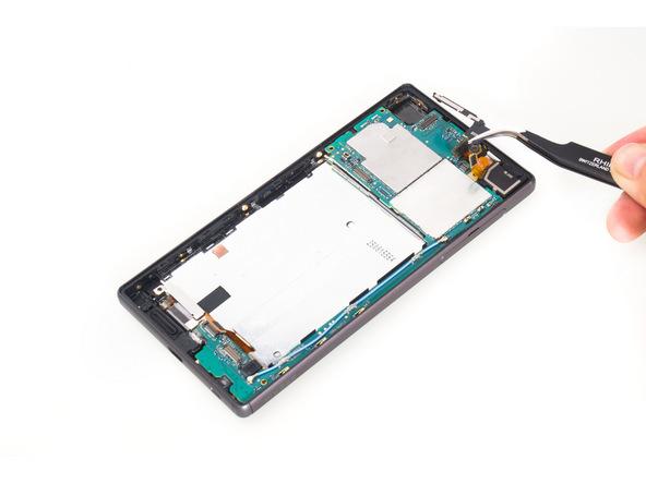 با نوک پنس برکت پشت لنز دوربین سلفی Xperia Z5 تعمیری را از روی آن بردارید.