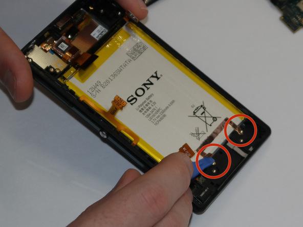 در زیر باتری اکسپریا ZL تعمیری یک گیره نصب است که منجر به ایجاد اتصال پایه (زمین) میشود. با نوک قاب باز کن پلاستیکی لبه های این گیره را از روی قاب گوشی آزاد کنید.