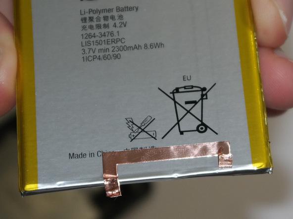 گیره اتصال به پایه (زمین) که روی لبه زیرین باتری اکسپریا ZL تعمیری نصب است را از روی آن جدا کرده و به باتری جدید منتقل نمایید.