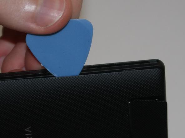 به آرامی پیک را به لبه های سمت چپ و راست درب پشت سونی اکسپریا ZL تعمیری هدایت کرده و این دو بخش را هم شل نمایید. در پایان سعی کنید با پیک درب پشت گوشی را به سمت بالا هدایت نمایید تا از روی بدنه گوشی بلند شود.