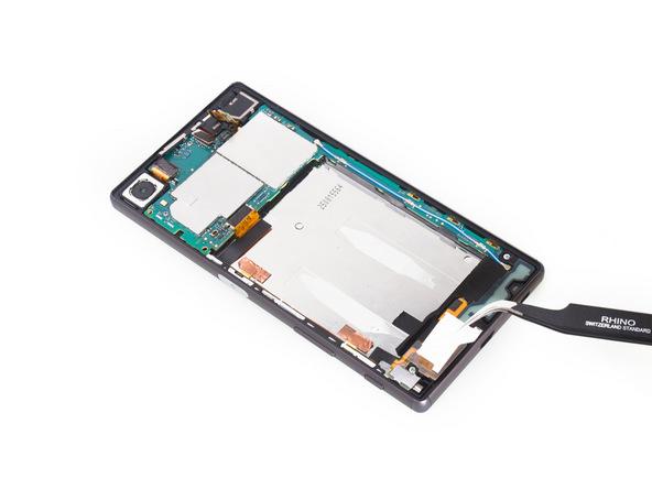 براکت روی اسپیکر Xperia Z5 تعمیری را با پنس از لبه زیرین قاب گوشی بردارید.