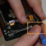 به آرامی نوک قاب باز کن پلاستیکی را از بخشی که در عکس دوم با رنگ نارنجی مشخص شده به زیر فلت دوربین و اسپیکر فرو برده و با هدایت آن به سمت بالا، این بخش را هم شل نمایید.