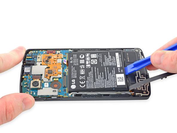 نوک قاب باز کن پلاستیکی را از لبه زیرین باتری به زیر آن فرو ببرید و خیلی آرام باتری را به سمت بالا هول دهید تا لبه زیرین آن مل عکس های ضمیمه شده از روی جایگاهش بلند شود.