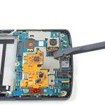 به آرامی نوک اسپاتول سر صاف را زیر کانکتور لنز دوربین اصلی Nexus 5 تعمیری قرار دهید و خیلی آرام آن را به سمت بالا هدایت کنید تا از روی سوکتش آزاد شود.
