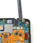 نوک اسپاتول سر صاف را زیر کانکتور لنز دوربین سلفی Nexus 5 که در گوشه سمت راست و فوقانی برد نصب شده قرار دهید و خیلی آرام آن را به سمت بالا هدایت کنید تا از روی سوکتش آزاد شود.