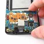 نوک اسپاتول را از سمت راست به زیر مادربرد Nexus 5 تعمیری فرو ببرید و این بخش از برد را از روی قاب گوشی بلند کنید. وقتی لبه برد از روی جایگاهش بلند شد، آن را با دست گرفته و به سمت عقب بکشید تا کاملا از قاب گوشی جدا شود.