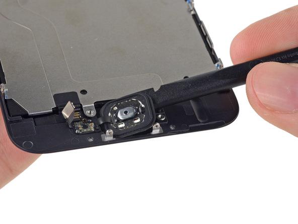 نوک اسپاتول را از سمت راست در زیر دکمه هوم آیفون تعمیری قرار داده.