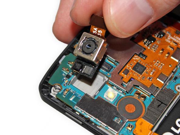 لنز دوربین اصلی گوشی را با دست یا پنس گرفته و کاملا از روی برد جدا نمایید.