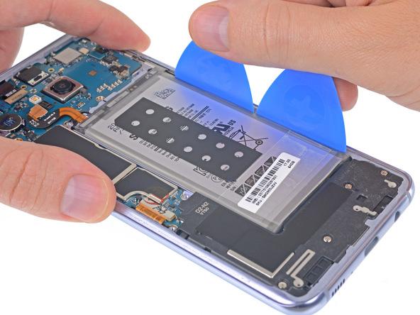 دو پیک را مثل عکس اول در شکاف لبه سمت راست باتری گلکسی S8 پلاس قرار دهید و به طور همزمان لبه آن ها را به سمت پایین هول دهید تا لبه سمت راست باتری از روی جایگاهش بلند شود.