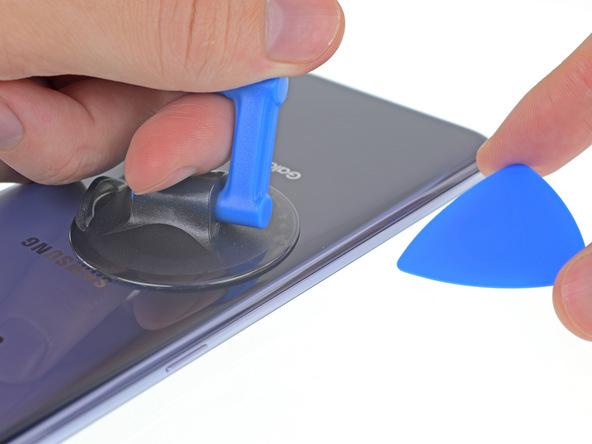 در همان حالت که ساکشن کاپ را ب سمت بالا کشیدهاید، نوک یک پیک را به درون شکافی فرو ببرید که روی لبه سمت چپ قاب گوشی ایجاد شده است.