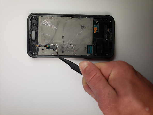 با نوک پنس خیلی آرام براکت روی کانکتور دکمه هوم گلکسی S7 Active تعمیری را از روی شیلد روی بدنه دستگاه جدا کنید.