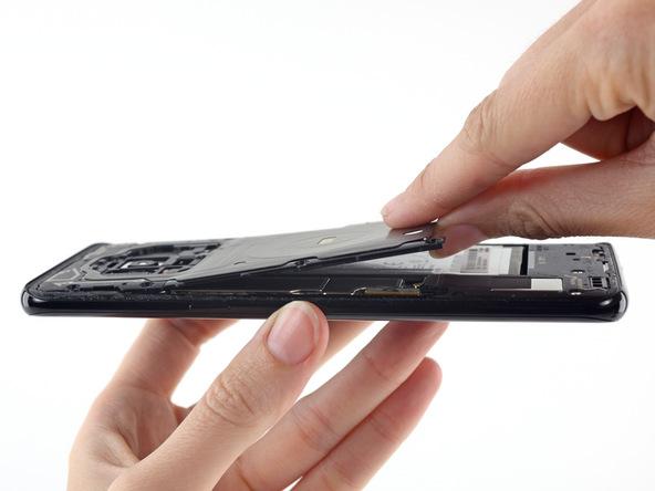 به آرامی لبه زیرین فلت NFC را با انگشت گرفته و به سمت بالا بکشید تا از روی بدنه دستگاه بلند شود.