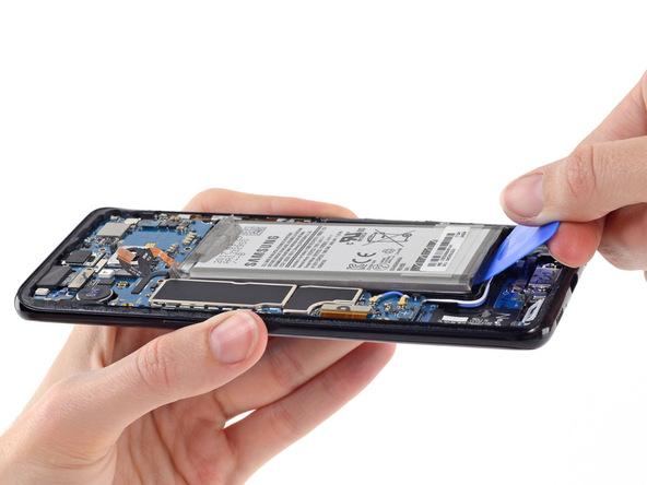 نوک یک پیک را خیلی آرام از لبه زیرین باتری به زیر آن فرو ببرید.