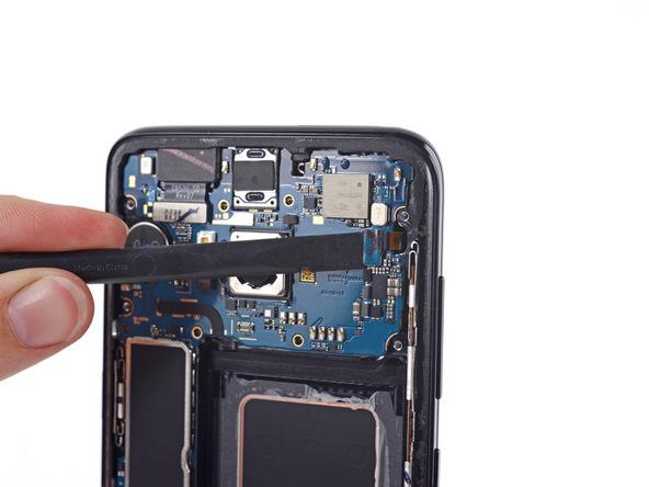 نوک اسپاتول را از سمت چپ به زیر کانکتور فلت سنسورهای گوشی فرو برده و آن را به سمت بالا هدایت کنید تا کانکتور مذکور از روی برد آزاد شود.